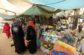 Women wait to buy things for Ramadan at a central food market in Khartoum, Sudan, July 18, 2012. Sudan's currency fell close to its historical low against the dollar as demand for imported food surged before the holy Muslim month of Ramadan, driving