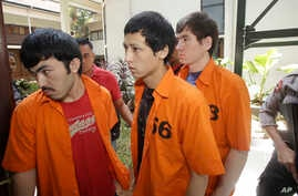 Suspected Islamic militants, from left to right, Abdulbasit Tuzer, Ahmet Mahmud and Abdullah are escorted by police officers prior to their trial hearing at North Jakarta District Court in Jakarta, Indonesia, Monday, July 13, 2015.