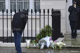 A man looks at floral tributes and messages left outside the home of former British prime minister Margaret Thatcher in London,April 9, 2013.