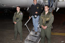U.S. Defense Secretary Leon Panetta, center,  steps off his jet after arriving at Yokota Air Base on the outskirts of Tokyo, Japan, Sunday, Sept. 16, 2012.