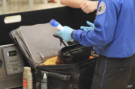 FILE-A Transportation Security Administration (TSA) official checks a passenger's carry-on luggage at a security checkpoint at Hartsfield-Jackson Atlanta International Airport in Atlanta,  Aug. 3, 2011.