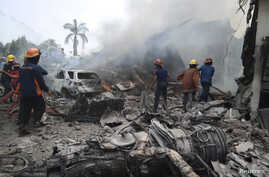 Firemen attempt to extinguish the fire surrounding the wreckage of an Indonesian military transport plane after it crashed in the North Sumatra city of Medan, Indonesia, June 30, 2015.