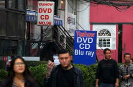FILE - People walk past a shop selling pirated movie DVDs and music CDs in Beijing, April 27, 2016.