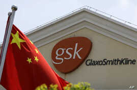 FILE - A Chinese flag is hoisted in front of a GlaxoSmithKline building in Shanghai, China. Police accused Peter Humphrey, a British executive of drug maker GlaxoSmithKline, on May 14, 2014, of leading a sprawling scheme to bribe doctors and hospital