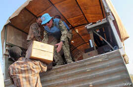 A handout photo released by the UNMISS shows peacekeepers of the United Nations distributing boxes of food to displaced people during a World Food Program (WFP) food distribution, Dec. 22, 2013.