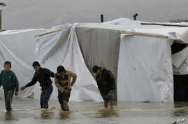 Syrian refugee boys make their way in flooded water at a temporary refugee camp, in the eastern Lebanese town of Al-Faour near the border with Syria, Jan. 8, 2013.