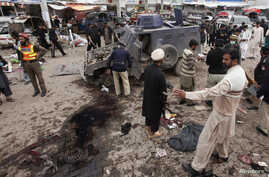 FILE: The Pakistani Taliban, fighting to topple the government through terrorist attacks, is dividing. In Peshawar, a sprawling city on Pakistan's border with Afghanistan, police gather evidence after a suicide bombing that killed at least nine bysta