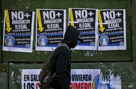 "A migrant walks past anti-migrant posters that read in Spanish ""No more illegal immigration. Solidarity begins at home."" prior to a march in favor of migrants, organized by the National Immigrants Coordinator, in Santiago, Chile,  Aug. 20, 2017."