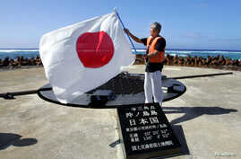 Tokyo Governor Shintaro Ishihara waves Japanese national flag as he visits at Okinotori island, about 1,700 km (1,056 miles) south of Tokyo and in the Pacific Ocean, May 20, 2005.