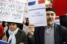 """Turkish citizens in France, one of them holding a booklet reading """"Electoral card"""", demonstrate in front of the Senate to protest against a law that would make it a crime to deny """"genocide"""" of Armenians, in Paris, Monday, Jan. 23, 2012."""