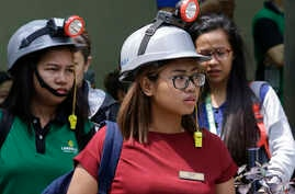 Office workers wear protective gear as they evacuate their building after an earthquake was felt in Manila, Philippines, Aug. 11, 2017. Office workers in the capital left their buildings but no damage was apparent after the quake struck about midday