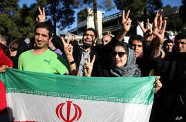 Iranians flash the victory sign as they hold their country's flag while waiting for arrival of Foreign Minister Mohammad Javad Zarif from Lausanne, Switzerland, at the Mehrabad airport in Tehran, Iran, April 3, 2015.