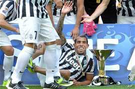 Juventus' Carlos Tevez, of Argentina, celebrates next to the Serie A trophy following the match between Juventus and Cagliari, Turin, Italy, May 18, 2014.