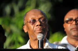 Former Haitian President Jean Bertrand Aristide speaks to supporters at the entrance to his home in Port-au-Prince, after giving a speech for the opening ceremony of the Lavalas Political Party, Sept. 30, 2015.