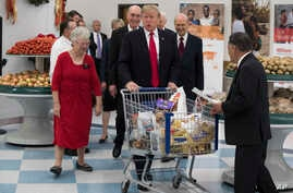 President Donald Trump pushes a cart during a tour of the Church of Jesus Christ of Latter-Day Saints Welfare Square food distribution center, Dec. 4, 2017, in Salt Lake City.