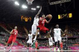 Tunisia's Makram Ben Romdhane (12) is defended by Nigeria's Koko Archibong (10) during the first half of a preliminary men's basketball game at the 2012 Summer Olympics, London, July 29, 2012.