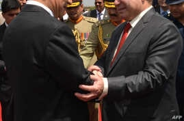 In this handout photograph released on April 20, 2015, by Pakistan's Press Information Department (PID), Chinese President Xi Jinping (L) shakes hands with Pakistan's Prime Minister Nawaz Sharif after arriving at Nur Khan air base in Rawalpindi.