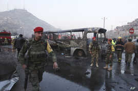 Afghan soldiers stand around a damaged bus at the site of a suicide attack by the Taliban in Kabul, Afghanistan, Saturday, Dec. 13, 2014.