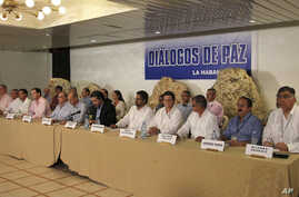 Representatives from Colombia's government negotiation team, left of center, and representatives from the Revolutionary Armed Forces of Colombia, or FARC, negotiation team, right side of table, issue a joint statement in front of a sign that reads in