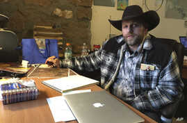 FILE - Ammon Bundy sits at a desk he's using at the Malheur National Wildlife Refuge in Oregon, Jan. 22, 2016.