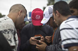 FILE - Migrants heading for Austria consult a map on a cell phone, in Budapest, Hungary, Sept. 5, 2015.