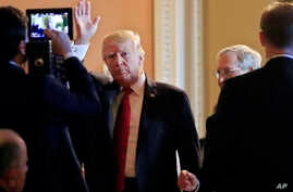 President Donald Trump, followed by Senate Majority Leader Mitch McConnell., waves as he arrives for a lunch with Republican senators at the Capitol in Washington, Oct. 24, 2017.