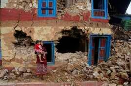 A Nepalese woman stands carrying her child outside her house damaged in last month's earthquake on the outskirts of Lalitpur, Nepal,  May 11, 2015.