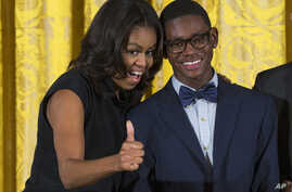 First lady Michelle Obama, pictured with Andre Massey of Deep Center Inc., Savannah, Ga., gives a sign of approval to the youth's father in the audience during the 2015 National Arts and Humanities Youth Program Awards at the White House, Nov. 17, 20