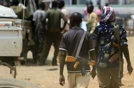 Armed men walk past on April 17, 2011 as resentment towards the capital Khartoum runs high in the restive town of Abyei, on the Sudanese north-south border, which suffers from chronic underdevelopment despite its strategic importance and the area's r
