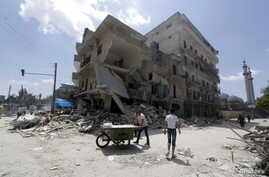 A man pushes a cart near damaged buildings in Aleppo's al-Saliheen district, May 2, 2015.