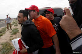 Pro-Trump rally participants yell at an anti-Trump protester as the two sides clash during the Southern California Make America Great Again march in support of President Trump, the military and first responders at Bolsa Chica State Beach in Huntingto