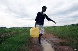 Woman carries water collected from a broken main water supply pipe in Kambuzuma, Harare (2009 photo)