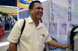 FILE - Political analyst Kem Ley smiles as he celebrated the 67th anniversary to commemorate the Kampuchea Krom territory's return to Vietnam by the French government, at Chroy Changvar, in Phnom Penh, Cambodia, June 4, 2016. Kem Lay was shot dead Ju...