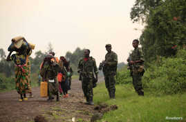 Displaced families walk past M23 rebels at Rumangabo, after government troops abandoned the town 23 km (14 miles)  north of the eastern Congolese city of Goma, July 28, 2012.