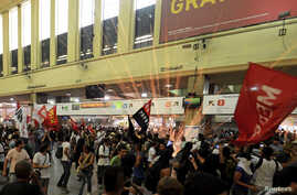 """A firework explodes as members of the """"Free Pass"""" movement invade the Central Train Station to demand zero tariffs in the Brazilian public transport system in Rio de Janeiro, Feb.6, 2014."""