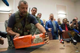 A pro-Russian fighter places a black box from the crashed Malaysia Airlines Flight 17 on a table while handing it over from Donetsk People's Republic officials to Malaysian representatives in the city of Donetsk, eastern Ukraine, July 22, 2014.