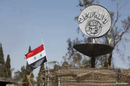 FILE - A Syrian national flag flutters next to the Islamic State's slogan at a roundabout where executions were carried out by IS militants in the city of Palmyra, in Homs Governorate, Syria, April 1, 2016.