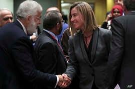 Libya's Foreign Minister Mohamed Taher Siala, left, shakes hands with European Union Foreign Policy chief Federica Mogherini during an EU-Arab League ministerial meeting at the European Council headquarters in Brussels, Monday, Feb. 4, 2019.