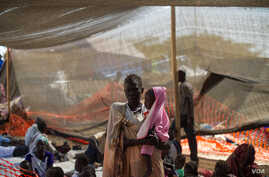 A woman stands with her daughter in the Médecins Sans Fron