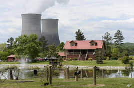 The Watts Bar Nuclear Plant cooling towers Unit 1, left, and Unit 2 rise near Spring City, Tenn., April 29, 2015. Construction of Unit 2 was started, abandoned, then restarted, becoming a cautionary tale for the power industry.