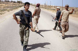 FILE - Libya Dawn fighters search for Islamic State militant positions during a patrol near Sirte.