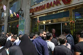 Iranians stand in front of a bank, hoping to buy U.S. dollars at the new official exchange rate announced by the government, in downtown Tehran, April 10, 2018. Iran moved this week to enforce a single exchange rate to the dollar, banning all unregul