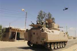 Egyptian Army soldiers in armored personnel carriers and a helicopter gunship patrol through a village in the northern Sinai Sept. 7, 2013.
