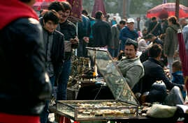 FILE - Uighur jade vendors sell their wares at an outdoor curio market where Chinese police have been checking their IDs everyday since a vehicle attack in Beijing, China.