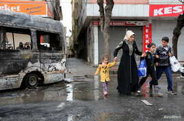 A woman with children walks by a vehicle, which was damaged during the clashes between security forces and Kurdish militants, in Baglar district, which is partially under curfew, in the Kurdish-dominated southeastern city of Diyarbakir, Turkey March ...