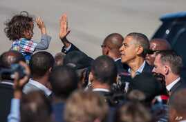 President Barack Obama high-fives with a child as he arrives at the Newport News/Williamsburg International Airport in Newport News, Va. October 13, 2012.