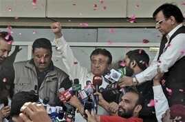 Former Pakistani President Pervez Musharraf, center, gestures to supporters upon arriving at the airport, Karachi, March 24, 2013.