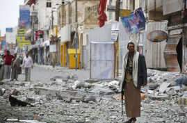 A Shiite fighter known as a Houthi stands guard in front of buildings destroyed by a Saudi-led airstrike in Sana'a, Sept. 5, 2015.