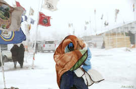 """A camper braces against high winds and a blizzard while walking inside the Oceti Sakowin camp as """"water protectors"""" continue to demonstrate against plans to pass the Dakota Access pipeline adjacent to the Standing Rock Sioux Reservation, near Cannon"""