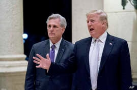 FILE - President Donald Trump, right, accompanied by House Majority Leader Kevin McCarthy, R-Calif., speaks to members of the media as they arrive for a dinner at Trump International Golf Club in West Palm Beach, Florida, Jan. 14, 2018.